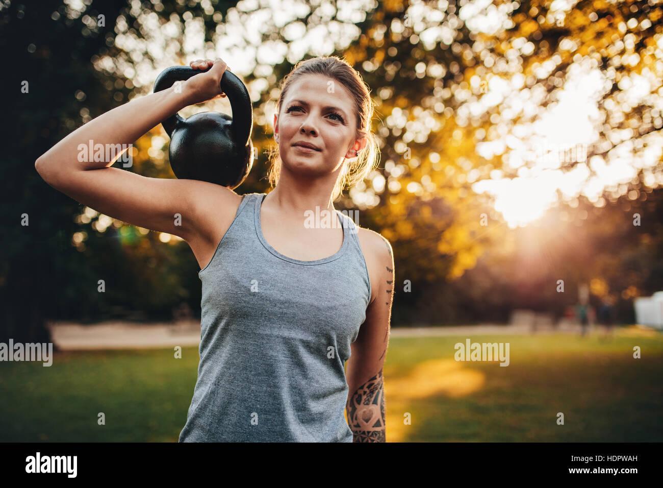 Portrait de jeune femme fit avec kettlebell poids dans le parc. Femme de remise en forme avec des poids de formation Photo Stock