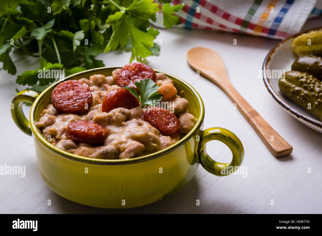 Ragoût de haricots avec de la saucisse au bol vert Photo Stock