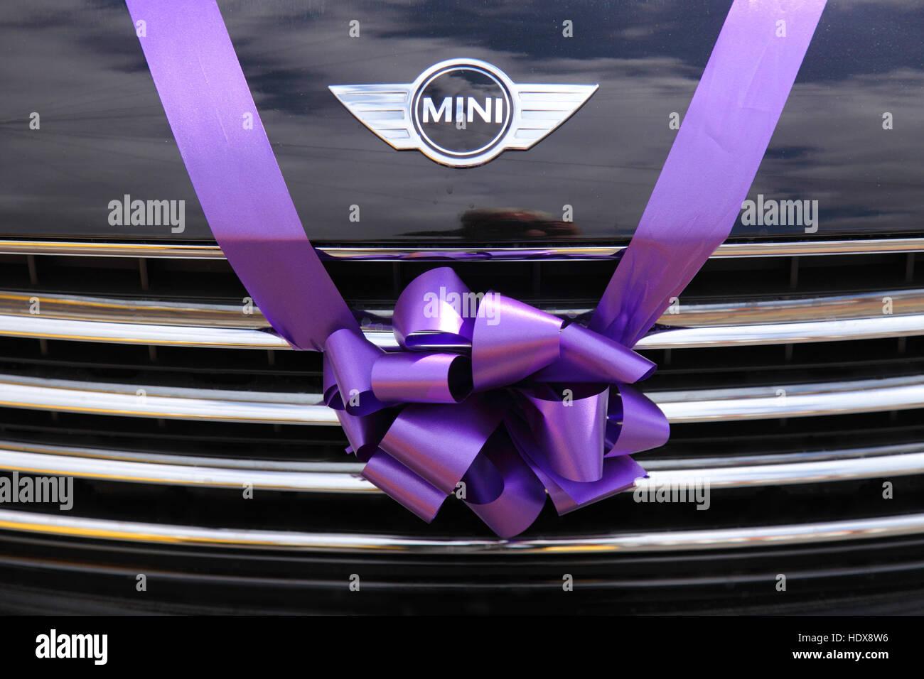 BMW Mini utilisé comme voiture de mariage, attachés avec un ruban violet rose et bow sur la calandre. Photo Stock