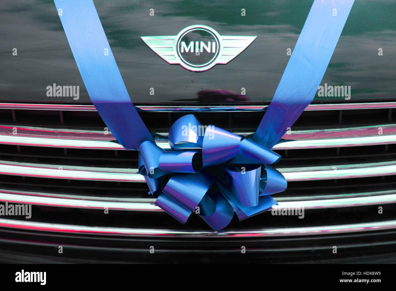 BMW Mini utilisé comme voiture de mariage, attachés avec un ruban bleu et bow sur la calandre. Photo Stock