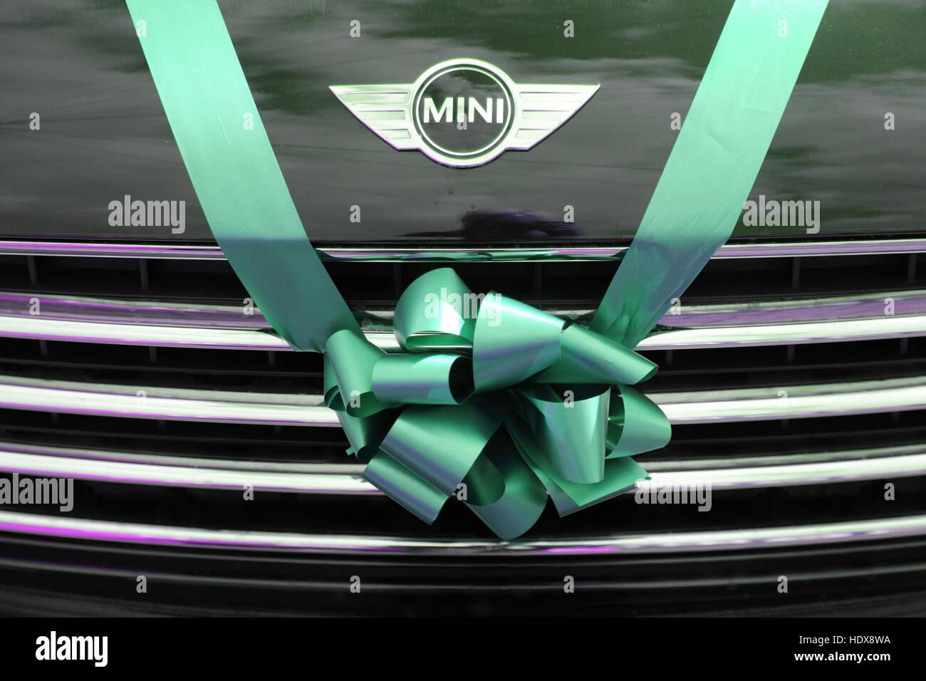 BMW Mini utilisé comme voiture de mariage, attachés avec un ruban vert et l'arc sur la calandre. Photo Stock