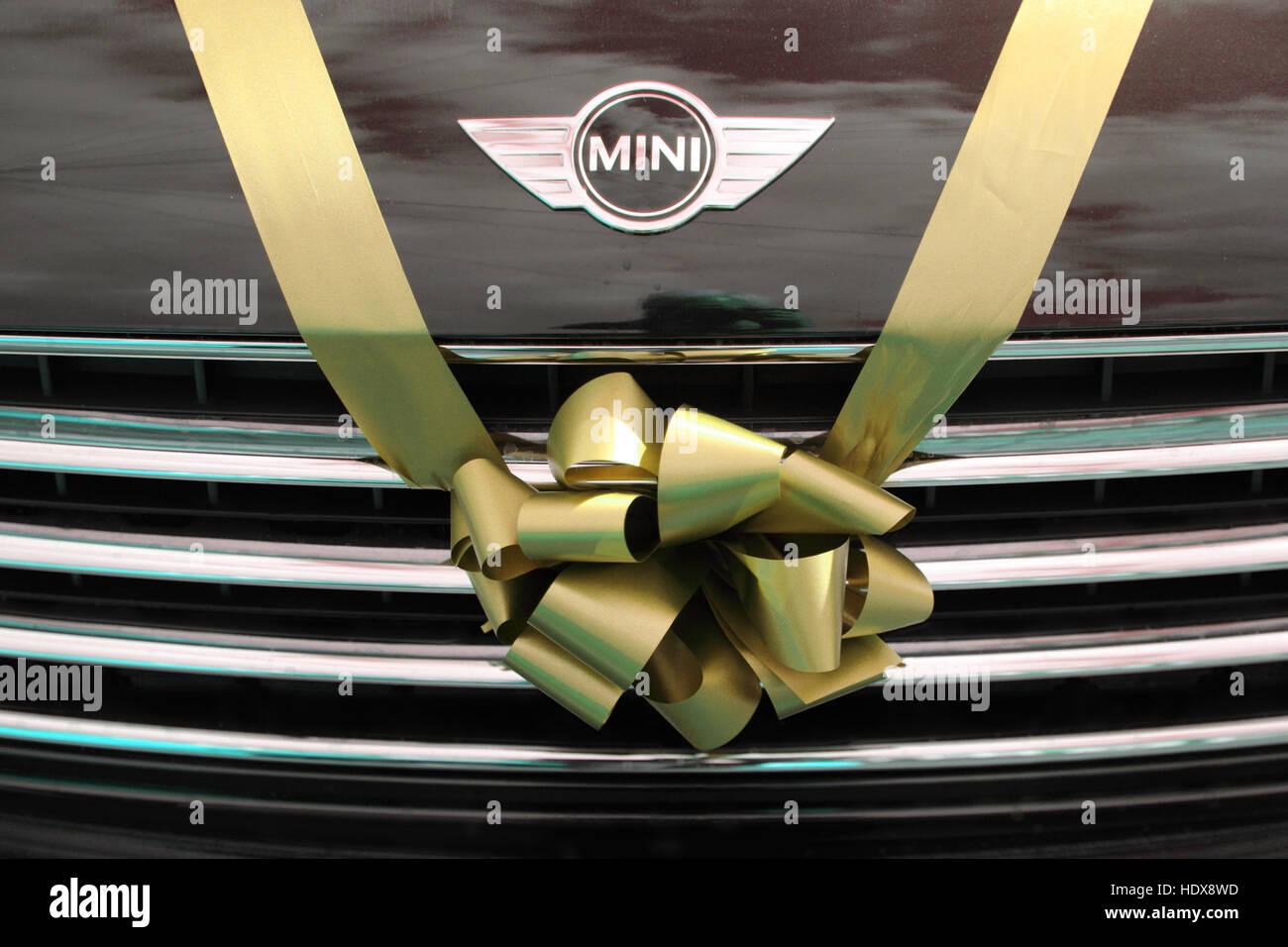 BMW Mini utilisé comme voiture de mariage, attachés avec un ruban jaune d'or et bow sur la calandre. Photo Stock