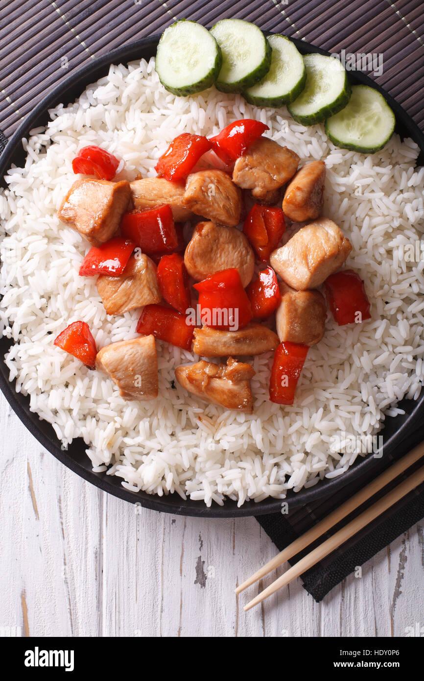 Riz avec morceaux de poulet en sauce sur une assiette close-up vertical Vue de dessus. Banque D'Images