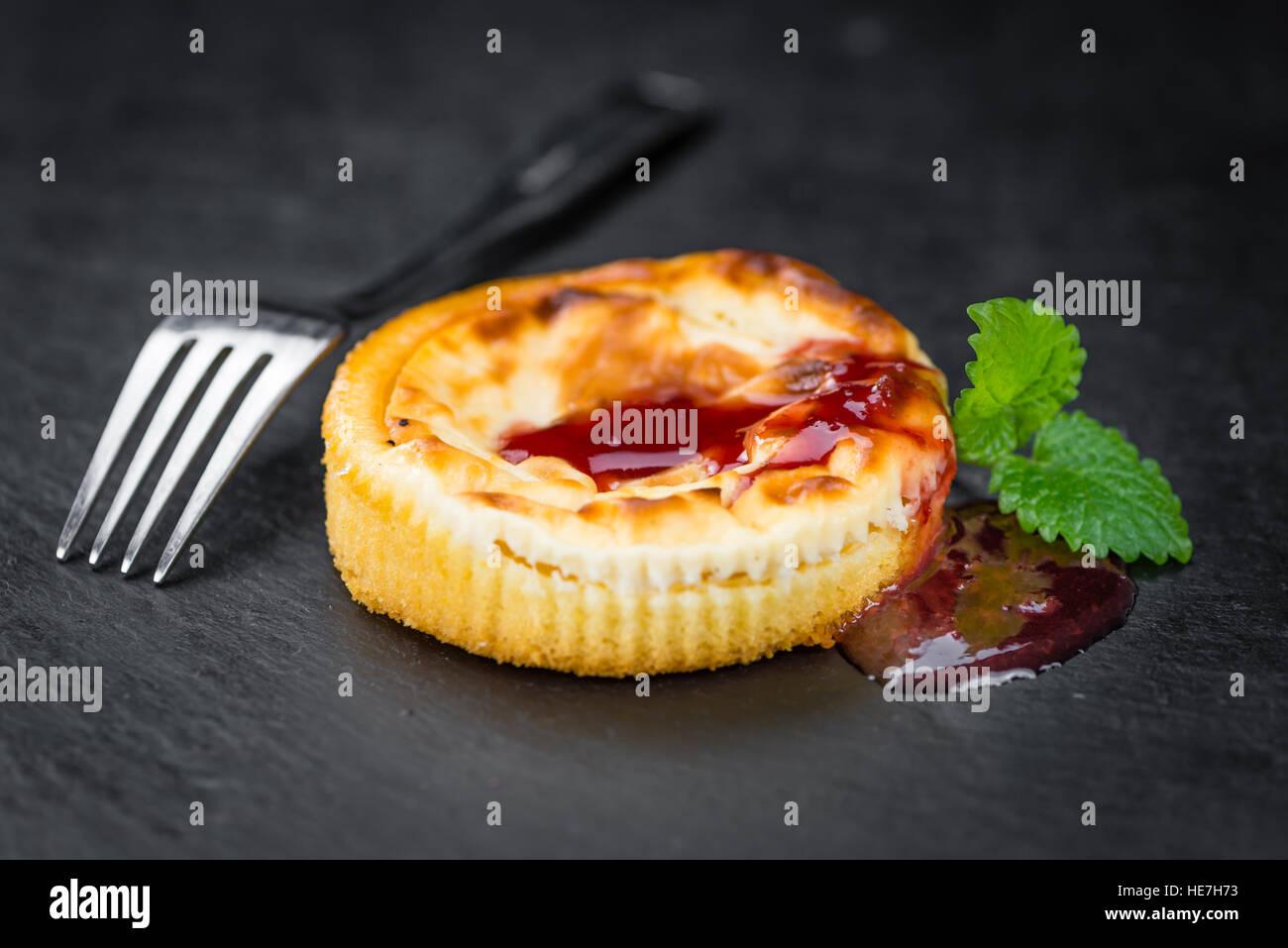 Mini Cheesecake frais (avec la sauce) sur un arrière-plan vintage (gros plan) Photo Stock