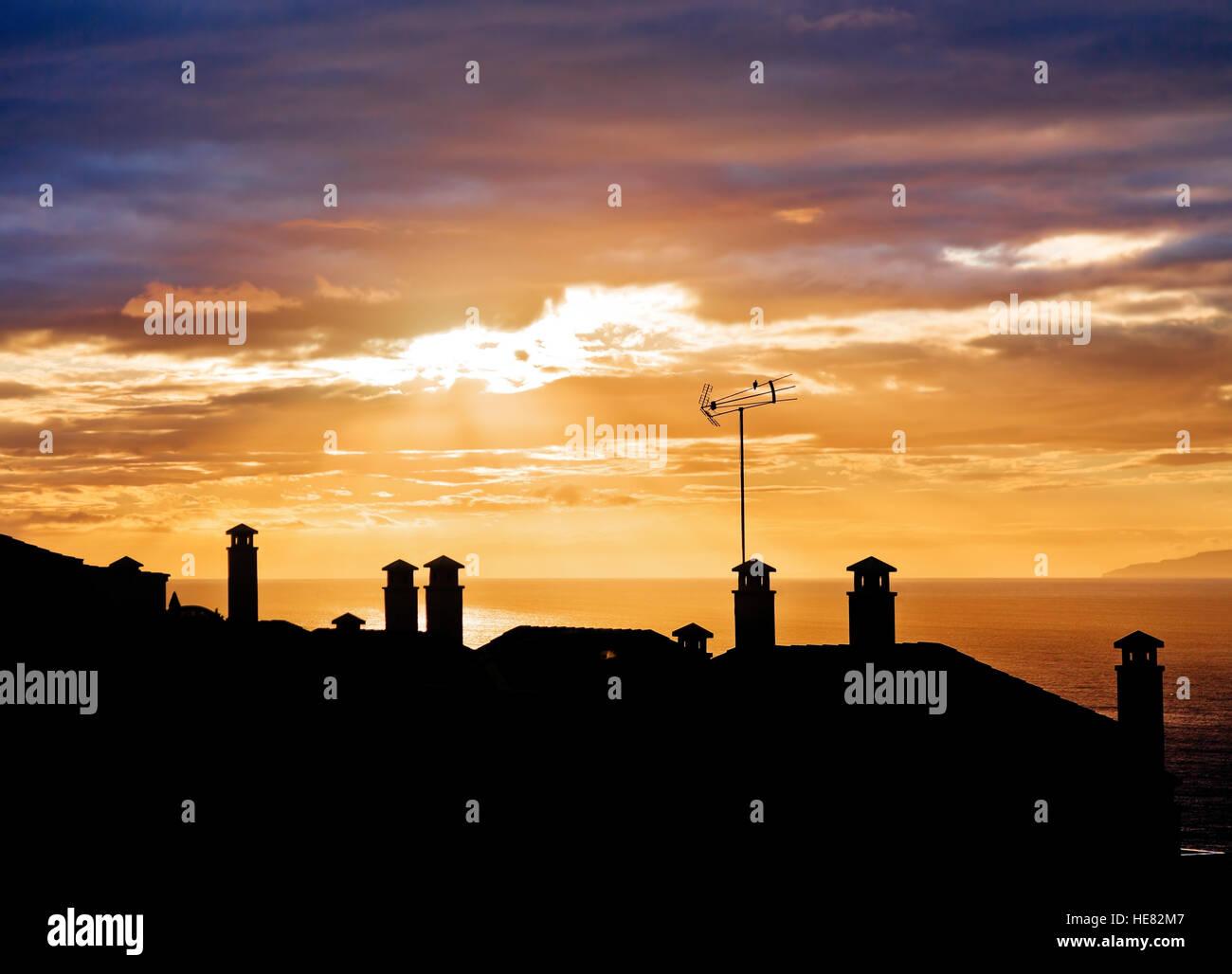 Coucher de silhouettes de toits de maisons avec cheminées Banque D'Images