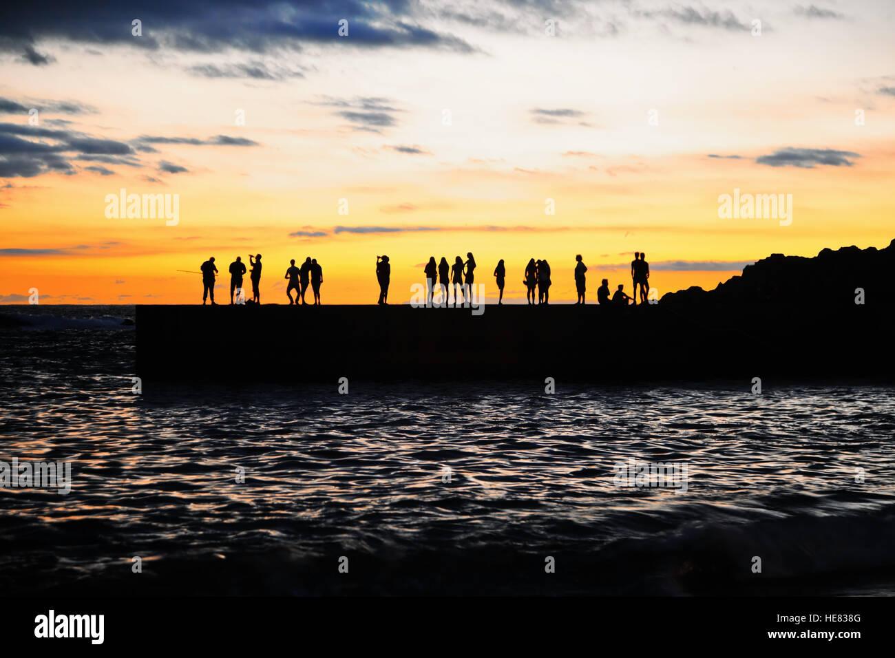 Les gens silhouettes sur le quai de la mer au coucher du soleil. Secteur de l'île de Ténérife. Espagne Banque D'Images