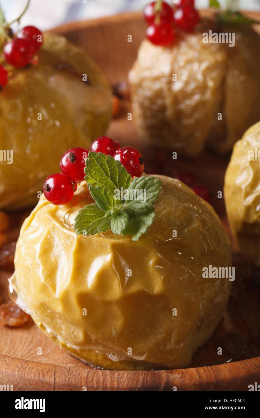 Des Pommes au four avec des groseilles rouges et menthe macro sur une plaque verticale. Photo Stock