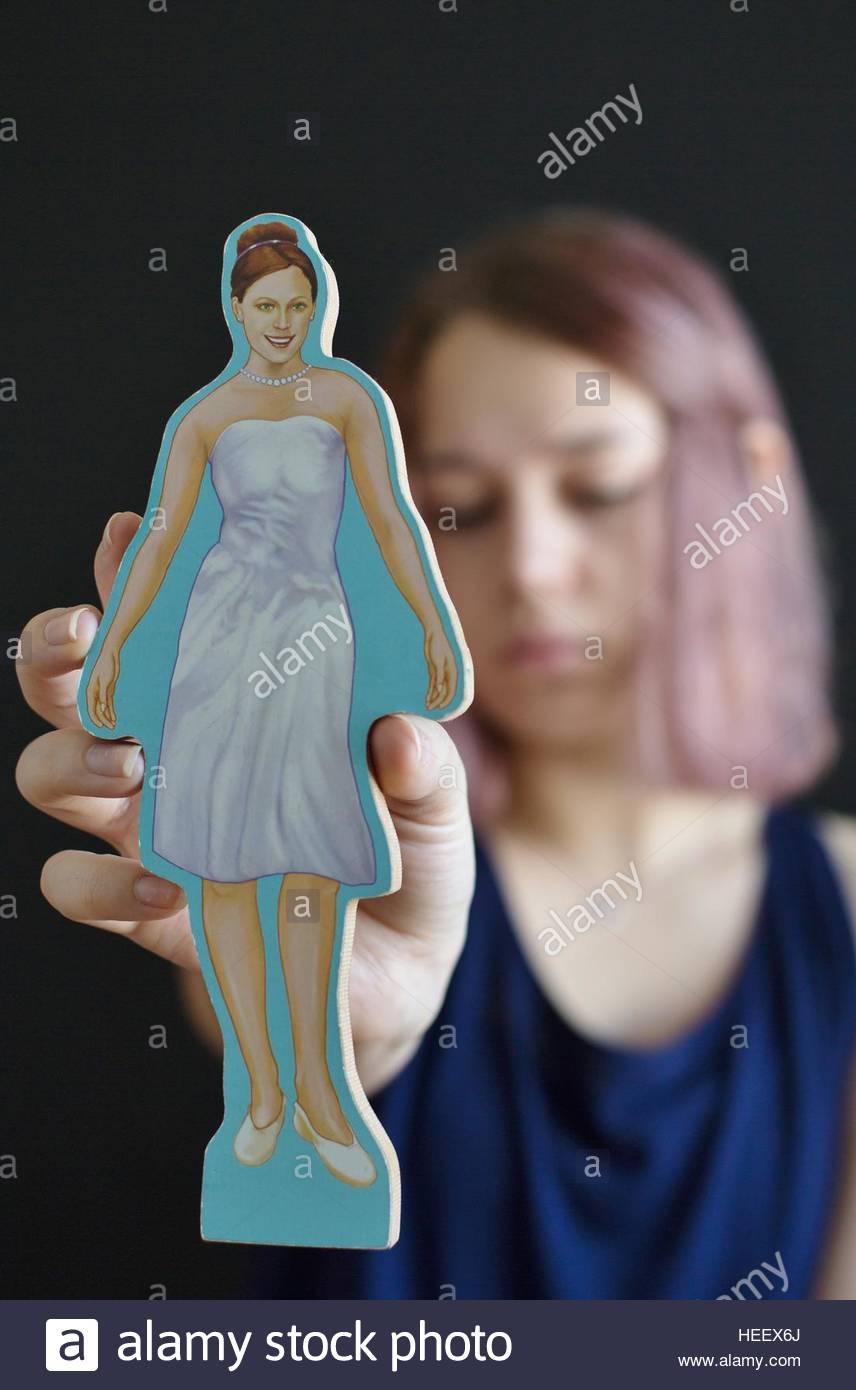 Une jeune fille tenant une découpe représentation d'une femme qui répond aux attentes de la société Photo Stock