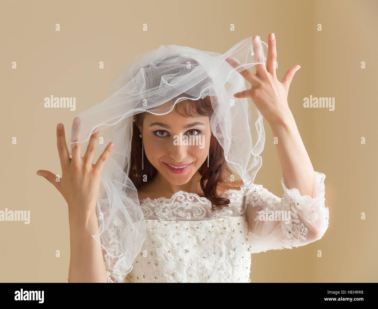 Photos de Studio une magnifique jeune femme en robe blanche et voile traditionnelle Photo Stock