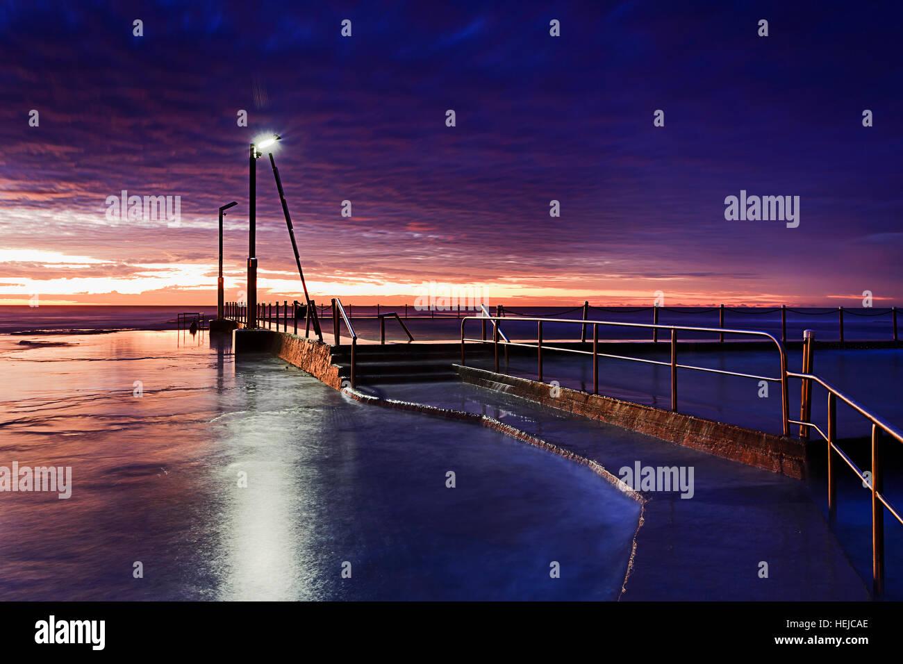 Lever du soleil sombre au-dessus de la piscine et de la plage de roche à Sydney Plages du Nord côte. Leadway Photo Stock