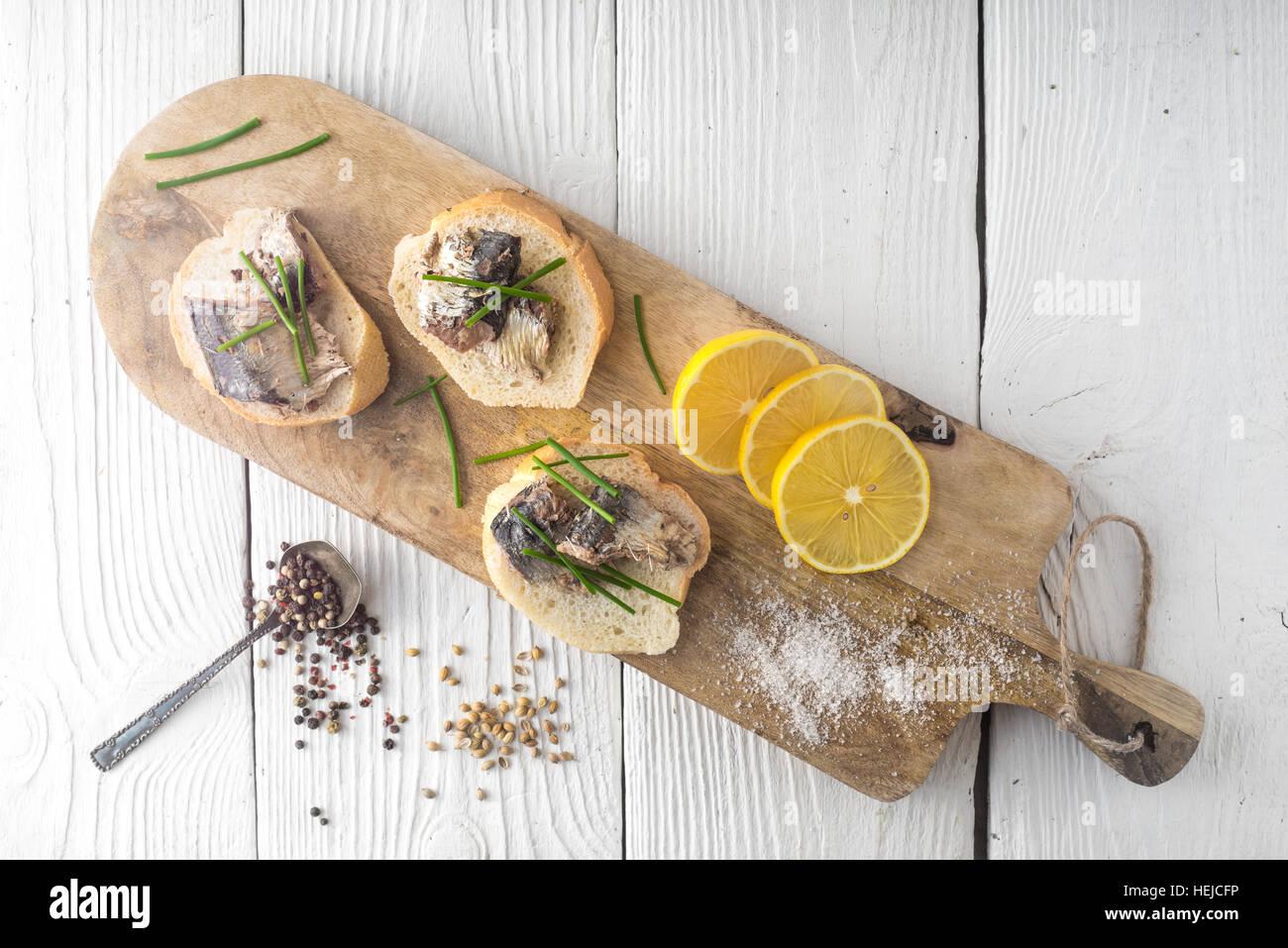 Des sandwichs avec des sardines sur une planche à découper Photo Stock