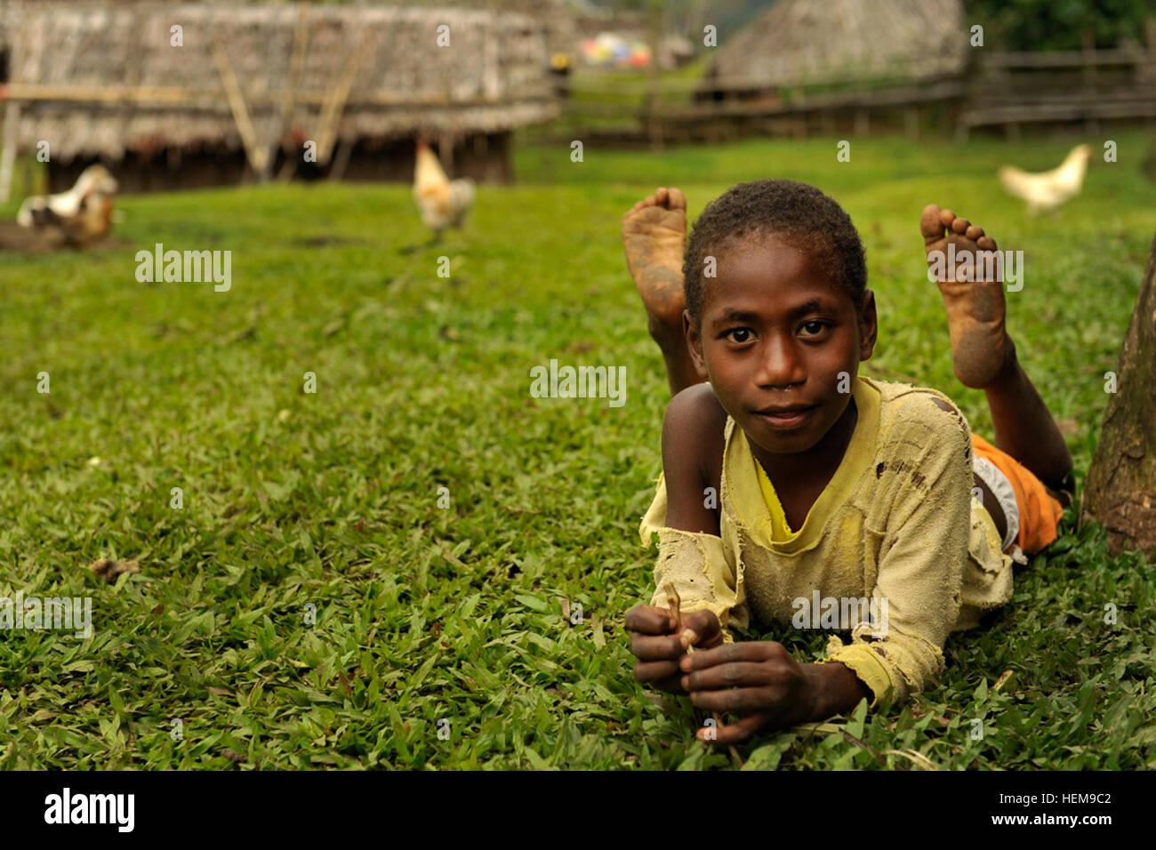 LUGANVILLE, VANUATU -- Un jeune garçon du village de Maljeah observe alors que les militaires et les civils Photo Stock