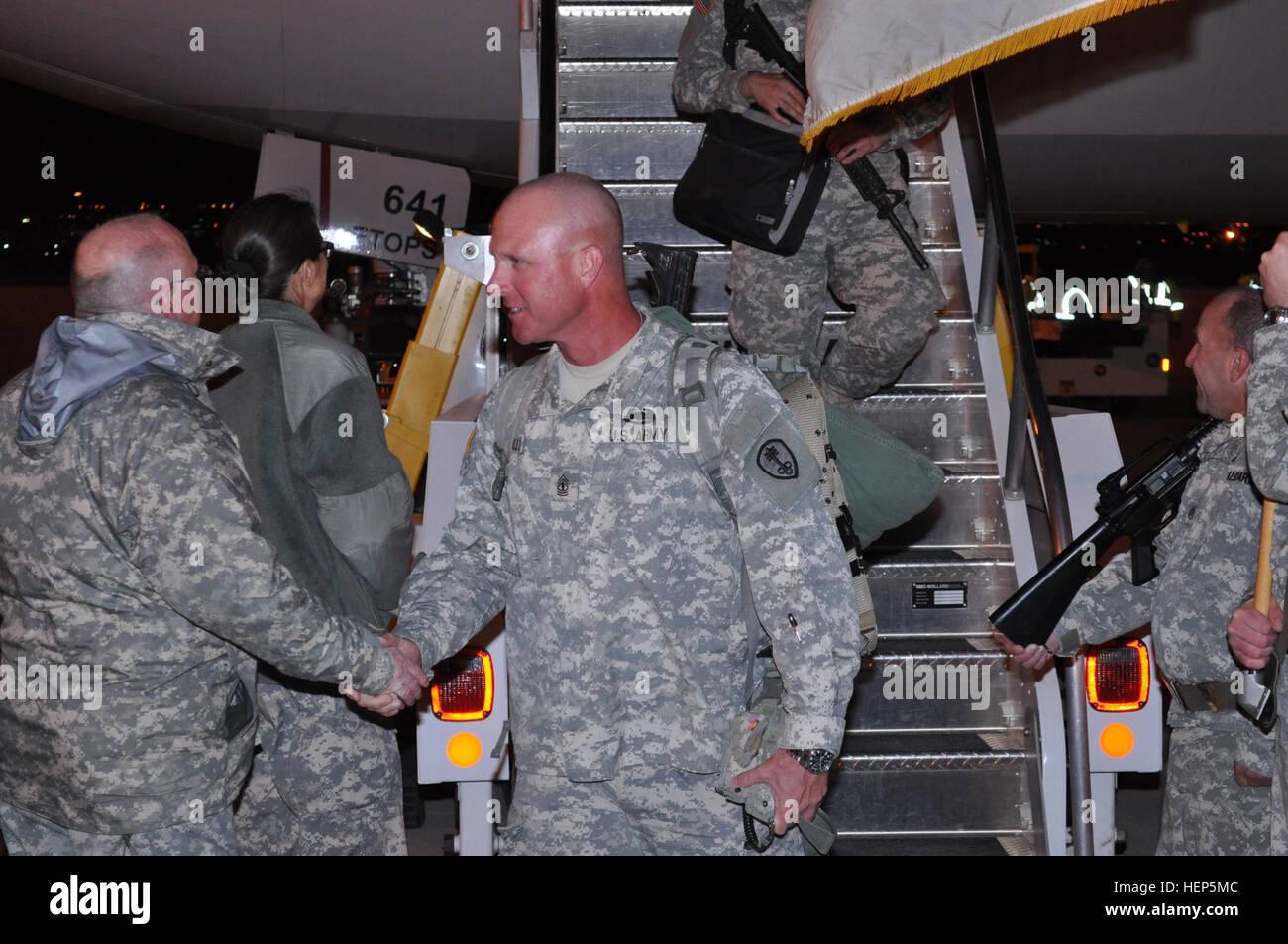 Premier Sgt. William Schultz, premier sergent, 342e Compagnie de Police militaire, est accueillie avec satisfaction de l'avion après son arrivée aux États-Unis à la Silas L. Copeland l'arrivée et le départ du Groupe de contrôle de l'air 10 févr. 26. Le 342MP Co. a terminé une période de neuf mois de déploiement des opérations détenu à Guantanamo Bay, Cuba. 342MP Company retourne du déploiement à Guantanamo Bay 150226-A-CX902-003 Banque D'Images