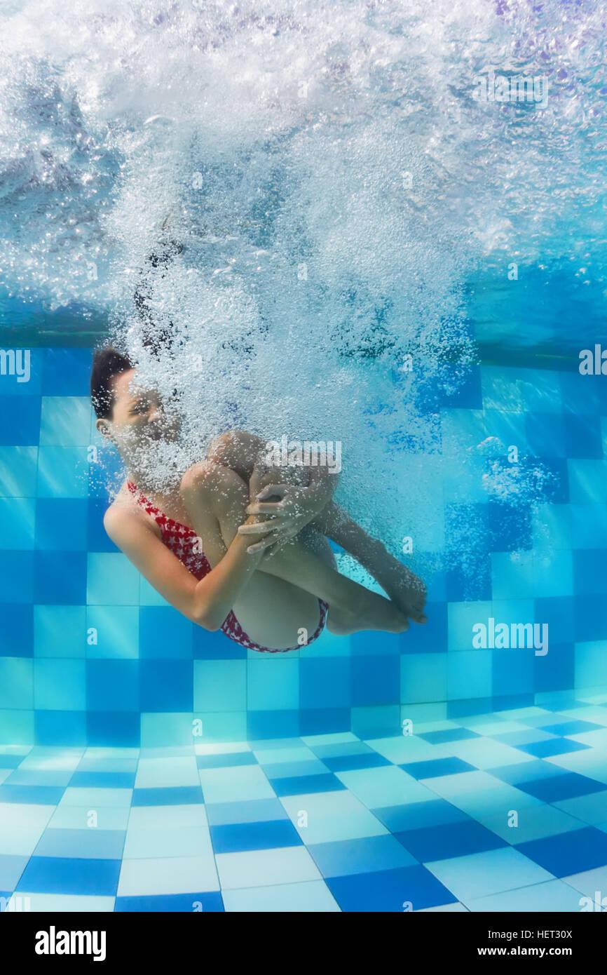 Funny face portrait of girl nager et plonger dans la piscine bleu avec plaisir - sauts au fond avec des touches Photo Stock