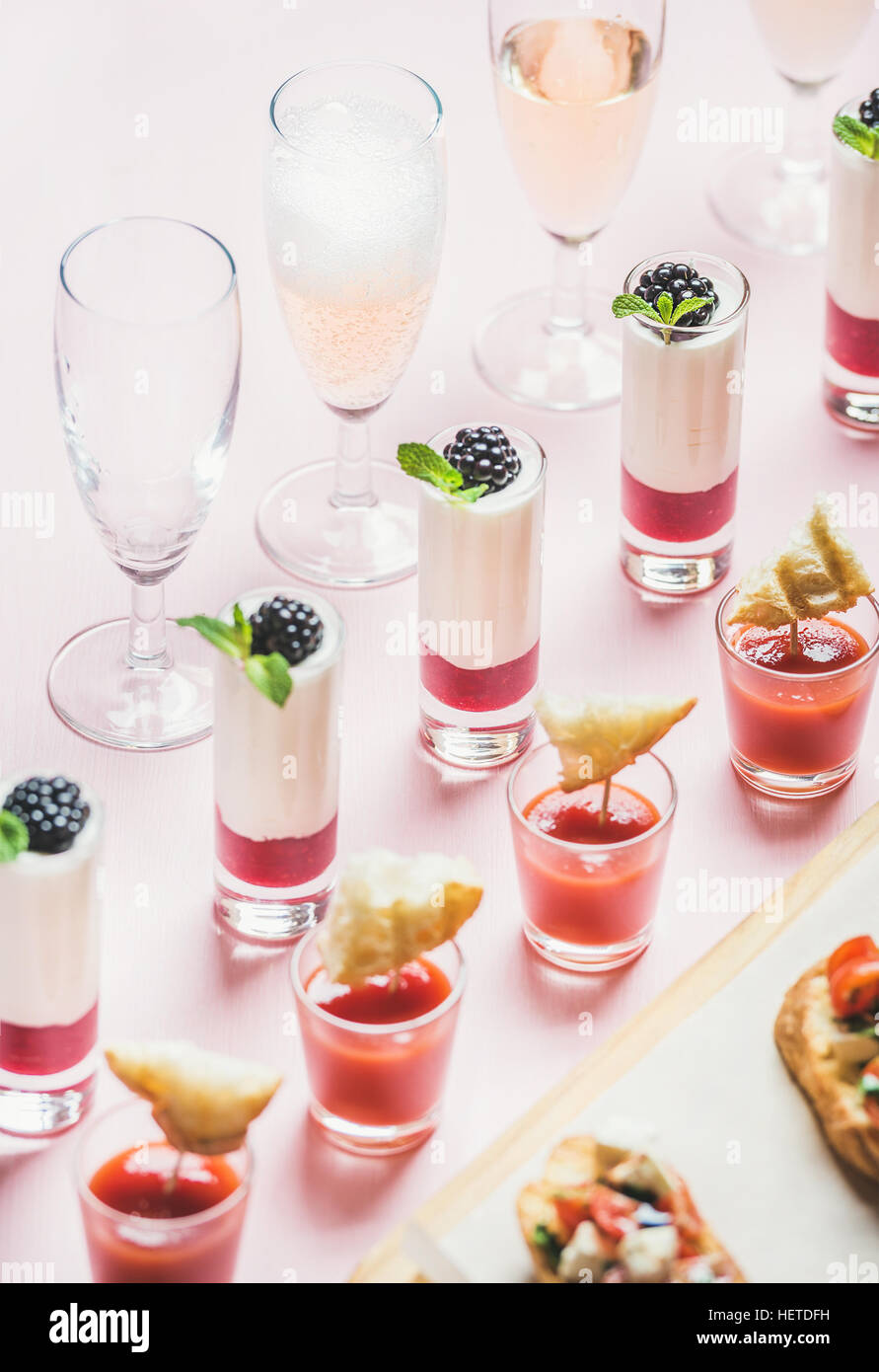 Des collations, des sandwiches, brushetta, gazpacho sur fond rose pastel desserts Photo Stock