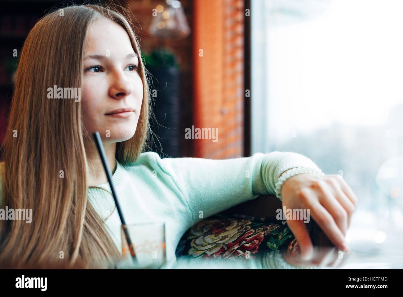 Photo d'une femme boire du jus d'une fenêtre Photo Stock