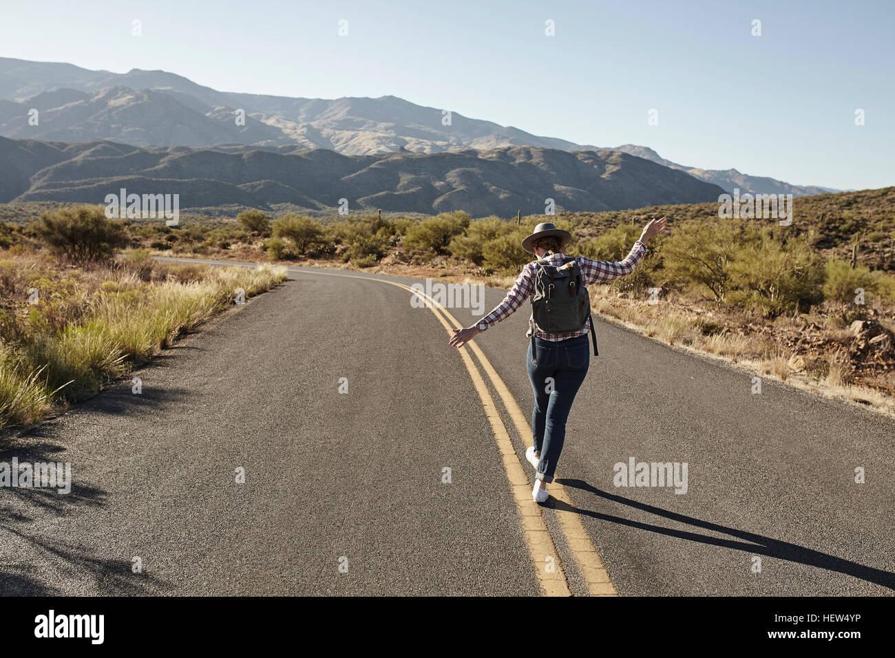 Femme marchant sur le marquage routier de route du désert, vue arrière, Sedona, Arizona, USA Photo Stock