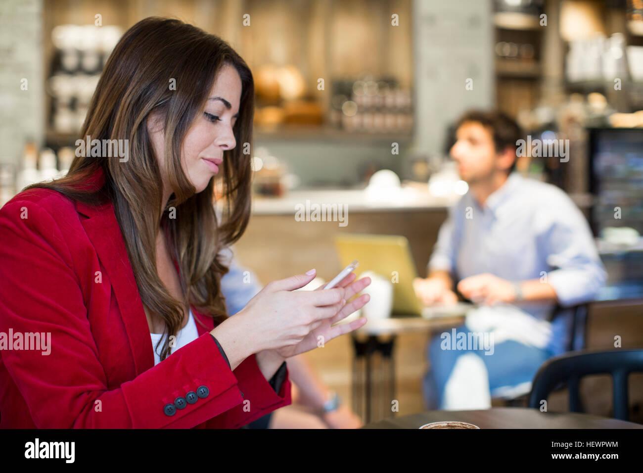 Jeune femme lisant des textes dans smartphone cafe Photo Stock