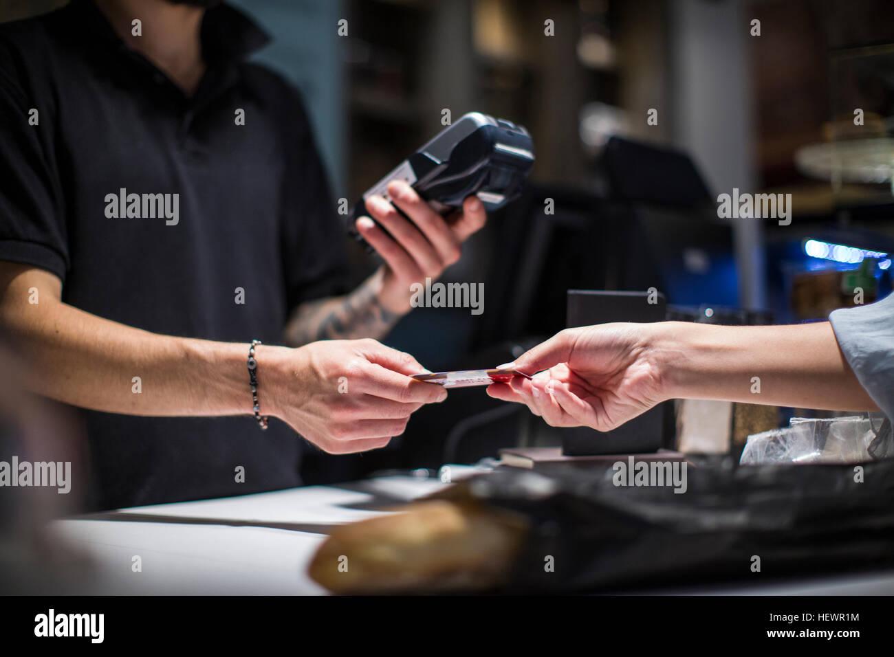 Close up of barista de remise d'une carte de crédit pour la clientèle féminine Photo Stock