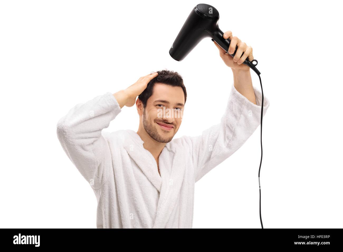 Jeune homme dans un peignoir en essuyant ses cheveux avec un sèche-cheveux isolé sur fond blanc Photo Stock