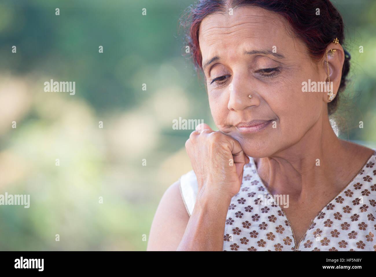 Closeup portrait dame âgée, morose, sombre, face au repos baissés sur la main, fond vert isolés Photo Stock