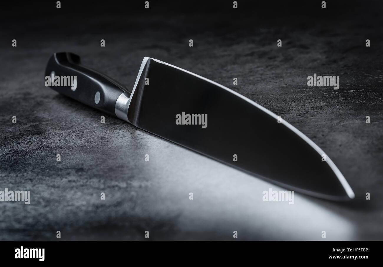 Couteau. Couteau de cuisine, couché sur une planche à découper moderne en béton. Photo Stock