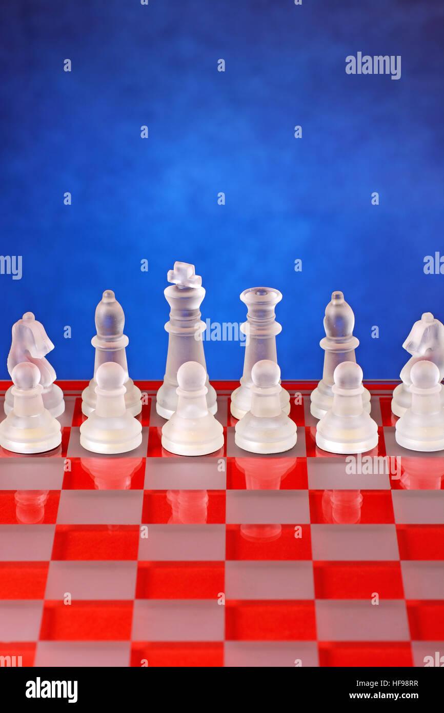 D'échecs en verre sur l'échiquier - Fond bleu Banque D'Images