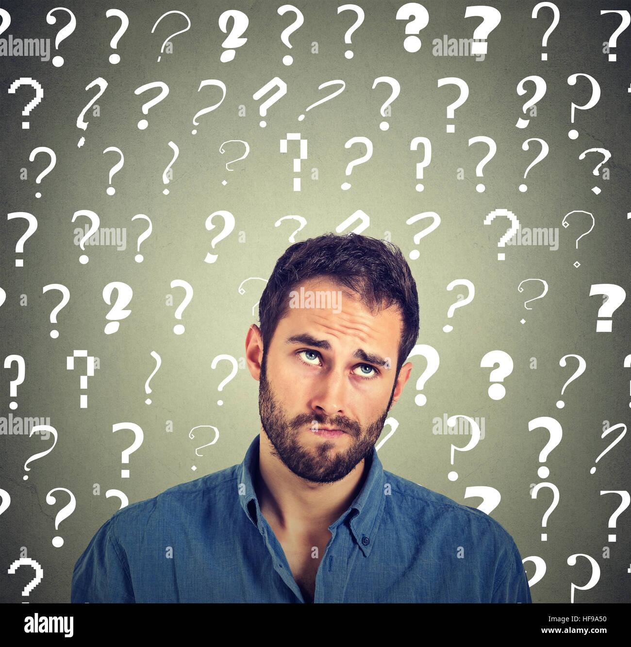 L'homme à la pensée confuse sceptique jusqu'intrigué beaucoup de points au-dessus de la tête isolé sur fond de mur Banque D'Images