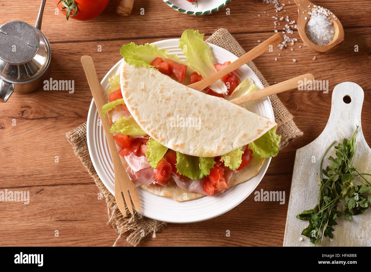 Piadina avec jambon, tomate et légumes - recette traditionnelle Italienne Photo Stock