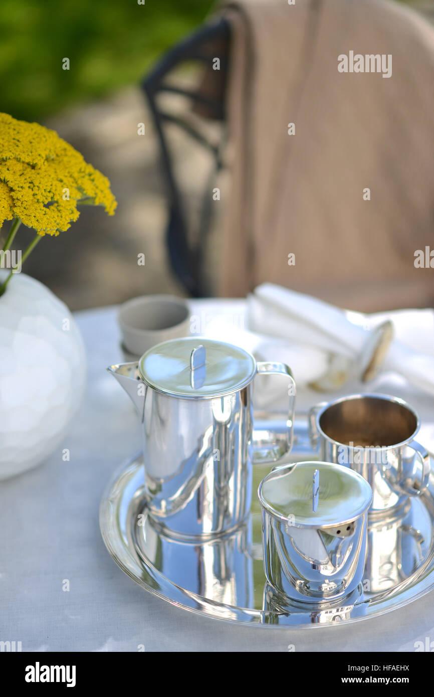 Black Coffee pot sur une table couverte de linge à l'extérieur en été. Banque D'Images