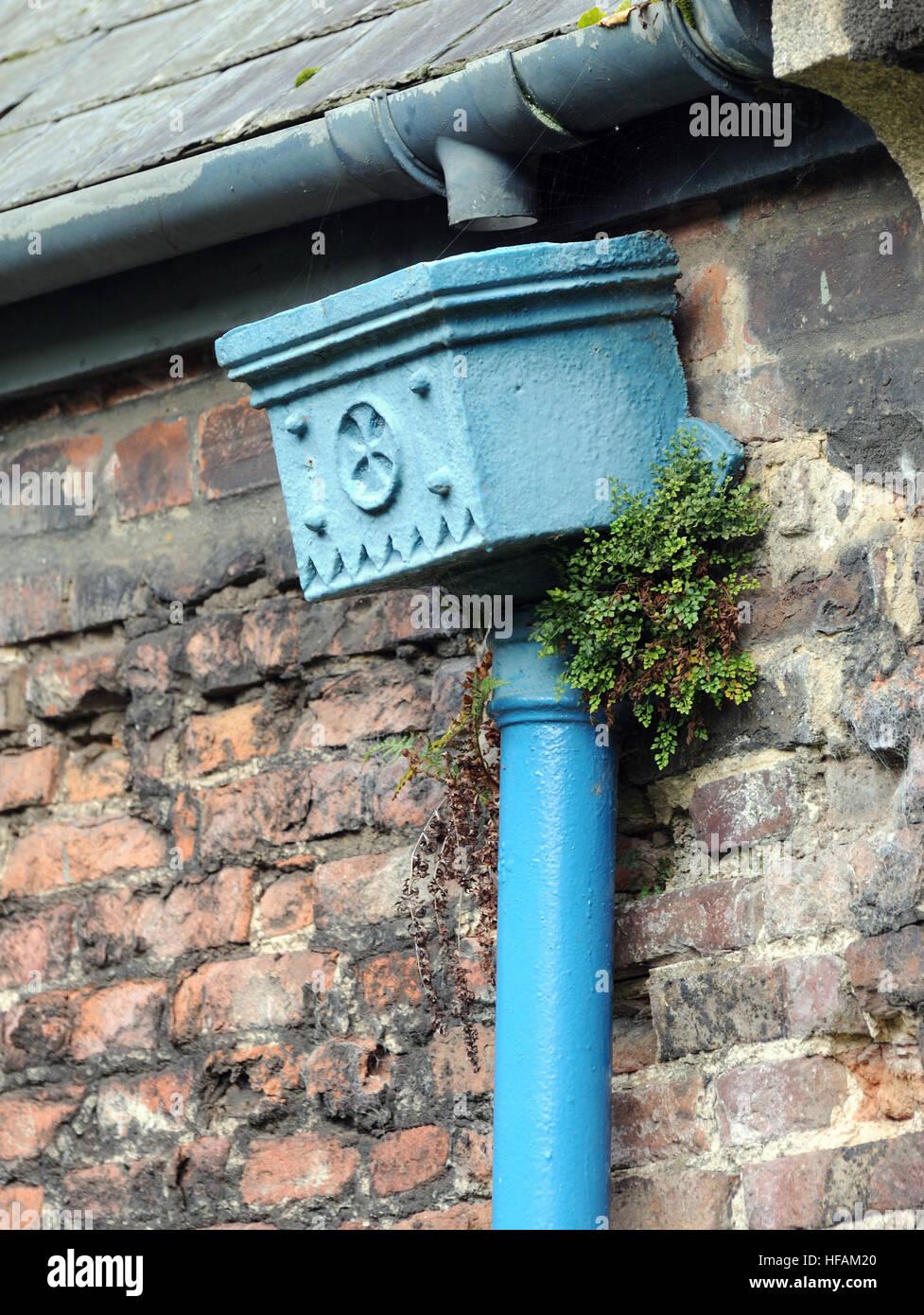 Une vieille fonte trémie pluie décorée d'une croix dans un cercle et peint en bleu. King's Photo Stock