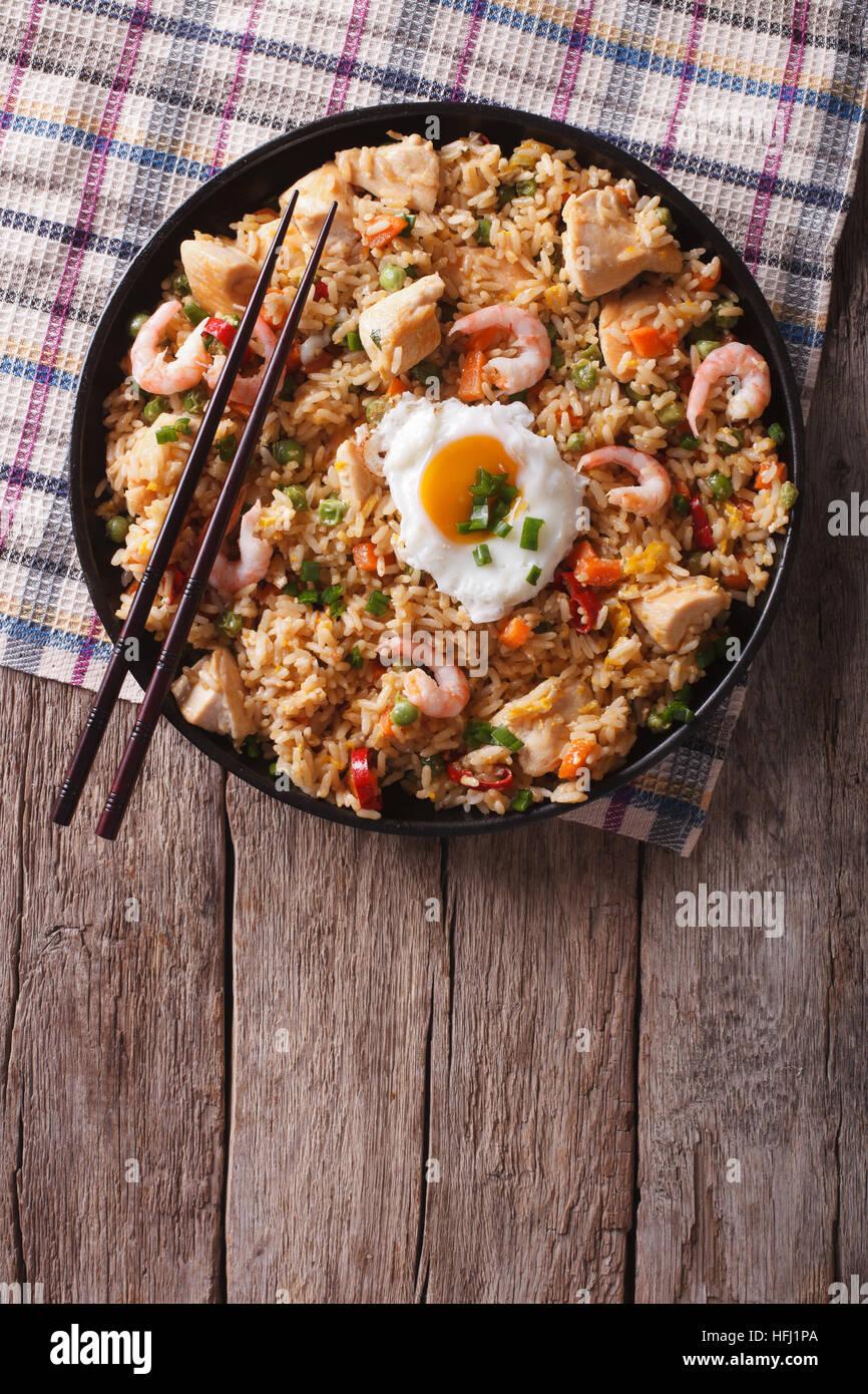 Riz frit asiatique nasi goreng au poulet, crevettes, légumes et oeufs vue verticale d'en haut Photo Stock