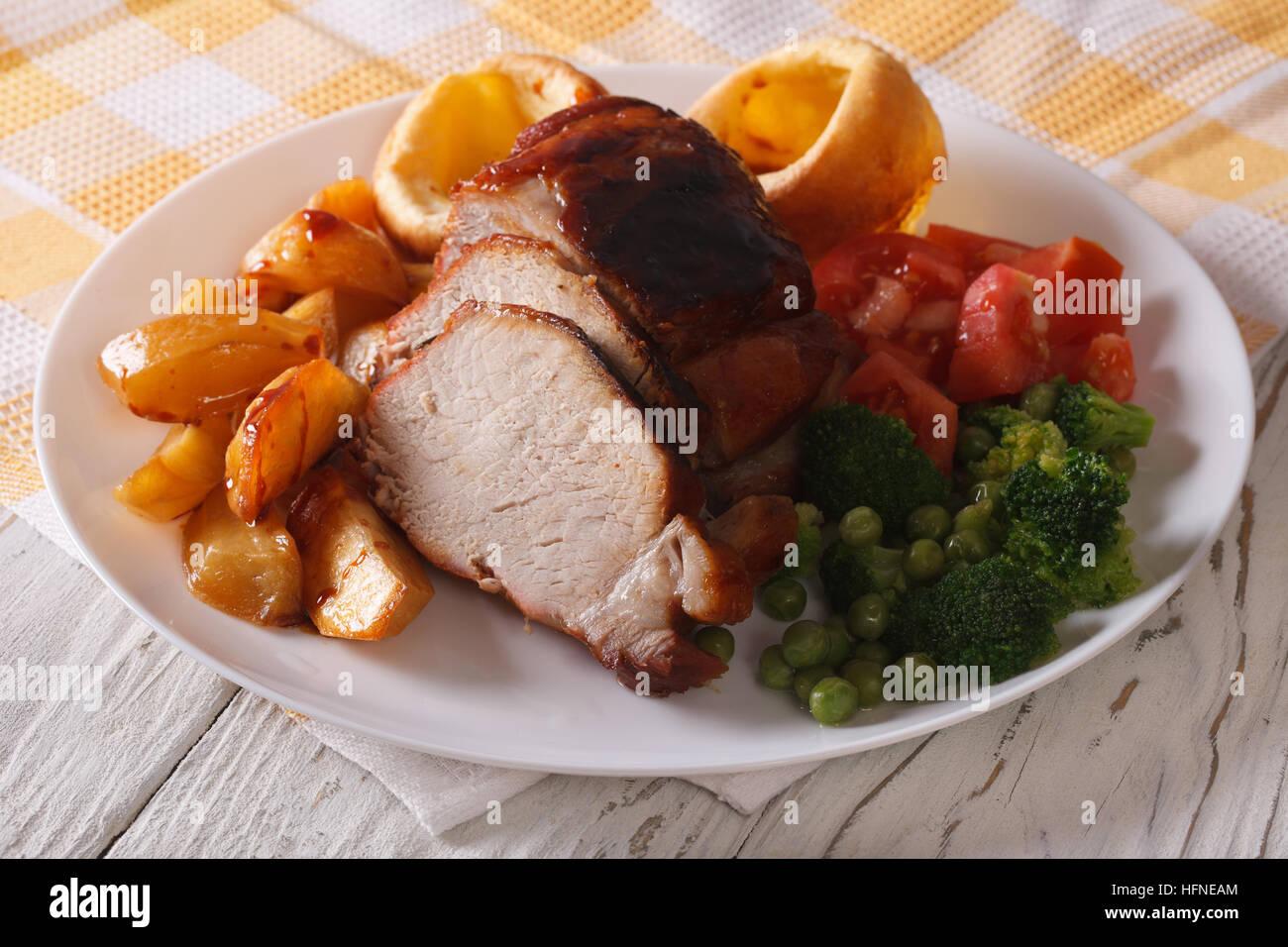 Le rôti du dimanche: porc aux pommes de terre, de légumes et de Yorkshire pudding gros plan sur Photo Stock