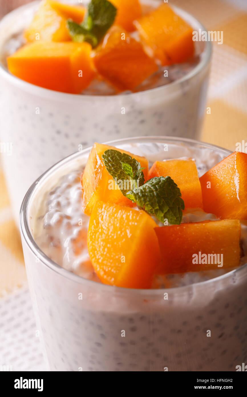 Les graines de Chia kaki avec du yaourt et un verre en macro. La verticale Photo Stock