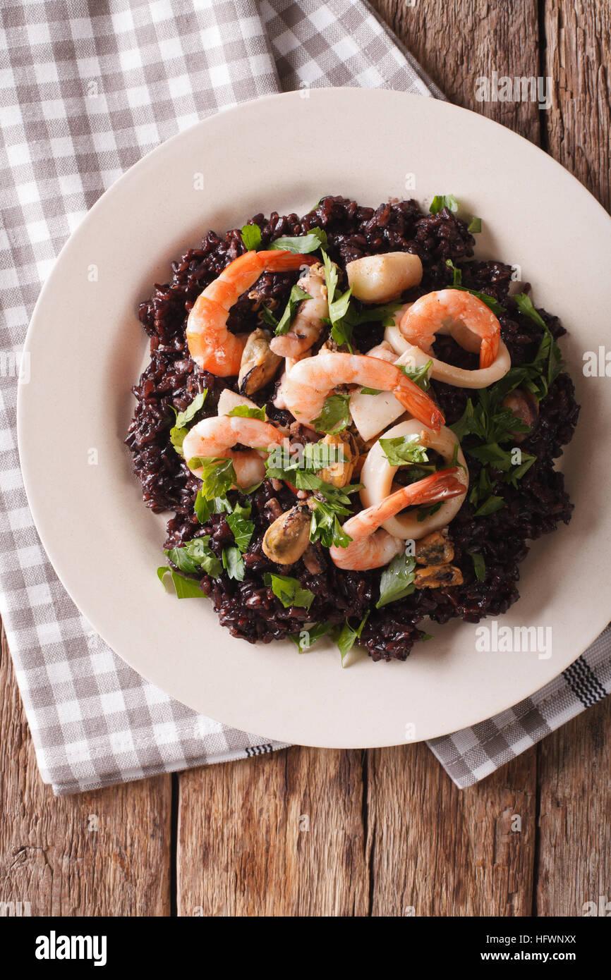 Le risotto de riz noir avec des fruits de mer gros plan sur une assiette sur la table. vertical Vue de dessus Photo Stock