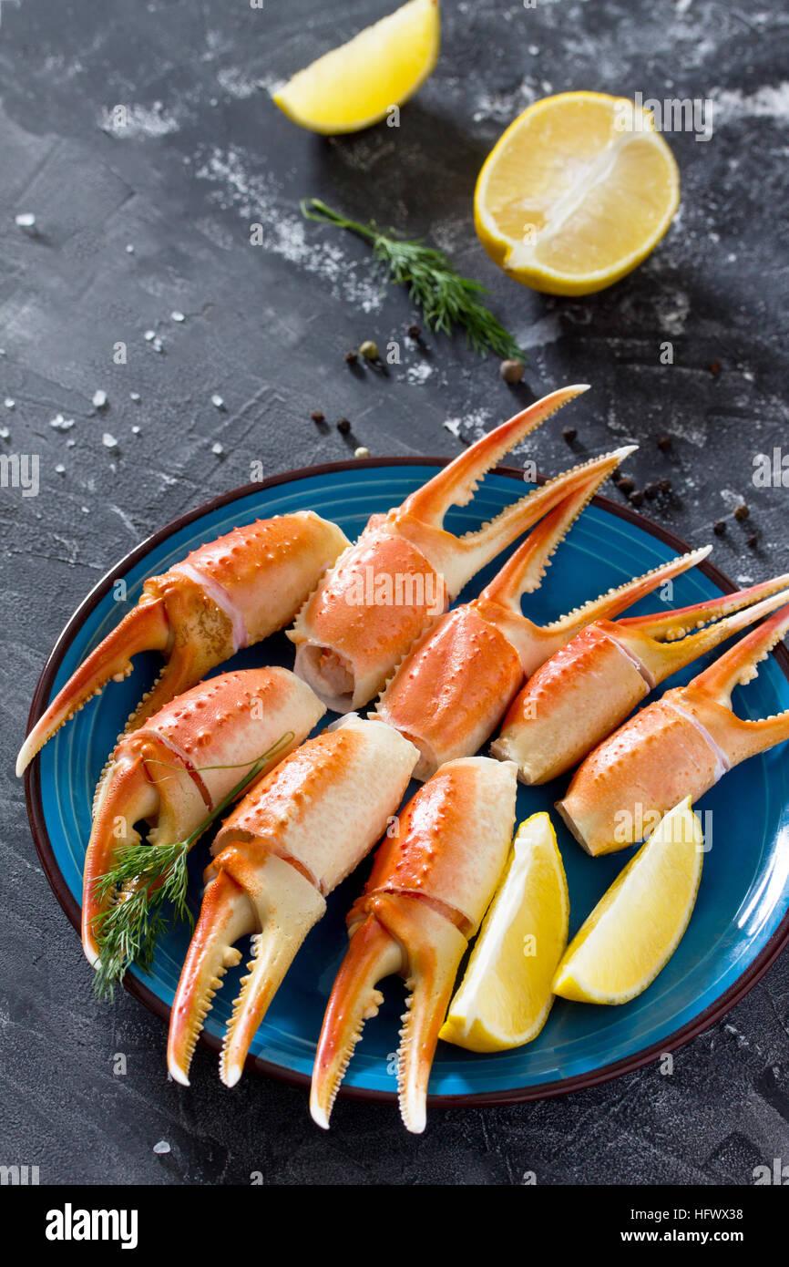 Pinces de crabe cuites avec du citron, sel de mer et poivre sur un fond en béton - concept de saine alimentation, Photo Stock