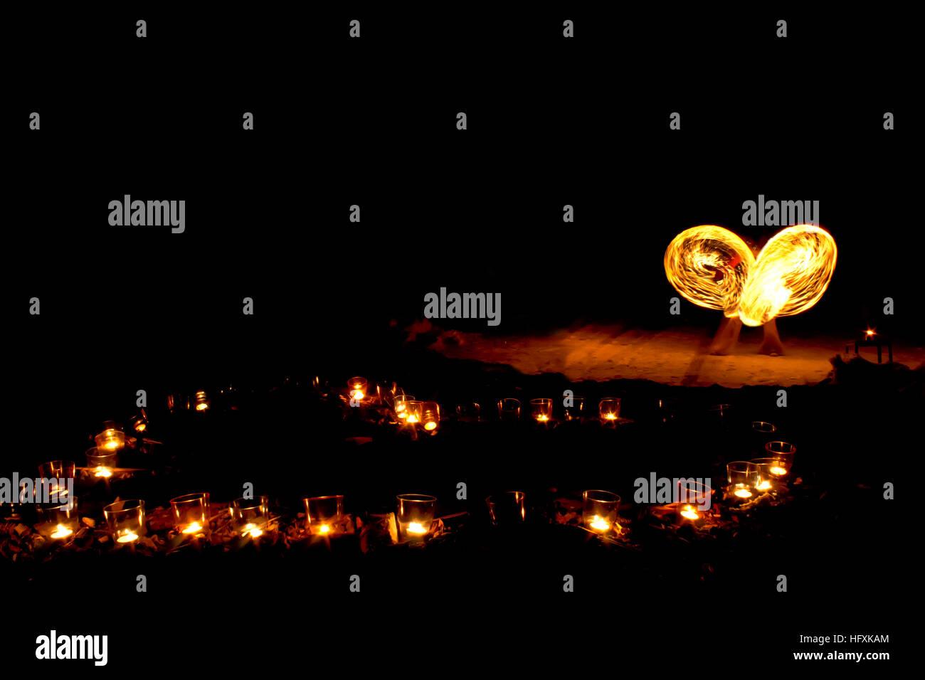Forme de coeur de brûler des bougies sur le sol, sur un fond de spectacle de feu. Banque D'Images