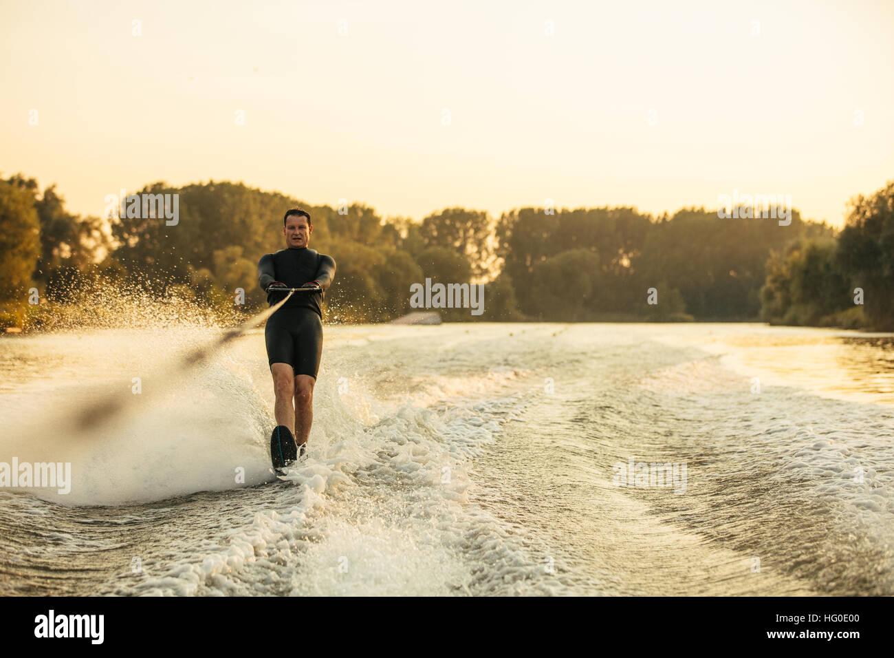Man riding planche sur vague de bateau à moteur. Homme ski nautique derrière un bateau sur le lac. Photo Stock