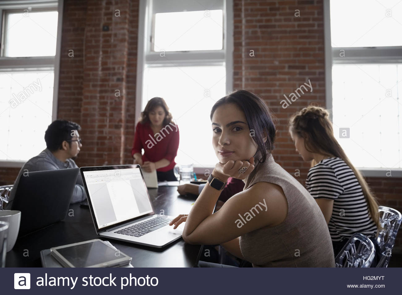 Portrait of smiling businesswoman using laptop in conference room meeting Photo Stock