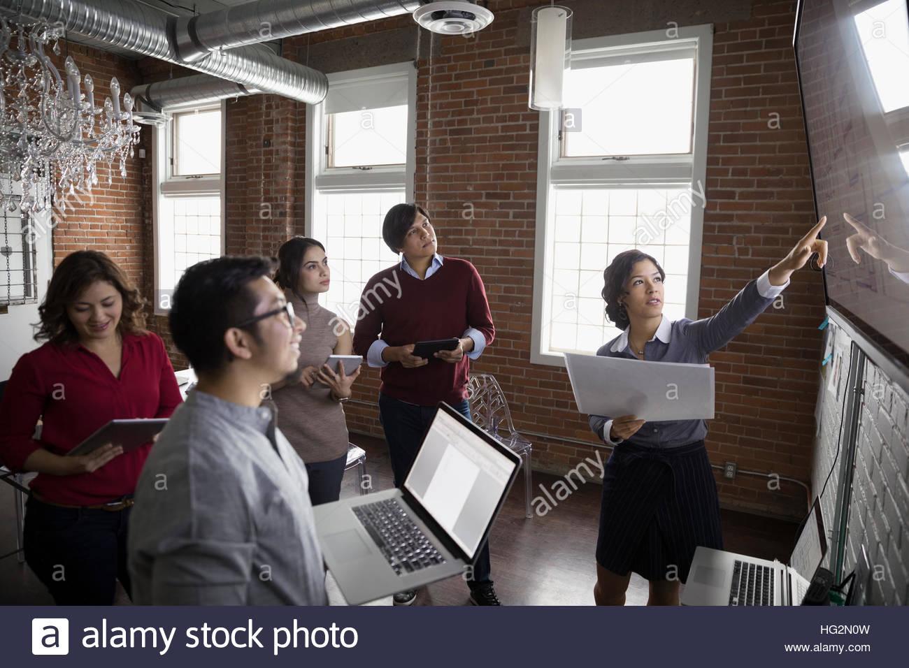 Designers hispaniques réunion au moniteur de télévision dans la salle de conférence Photo Stock