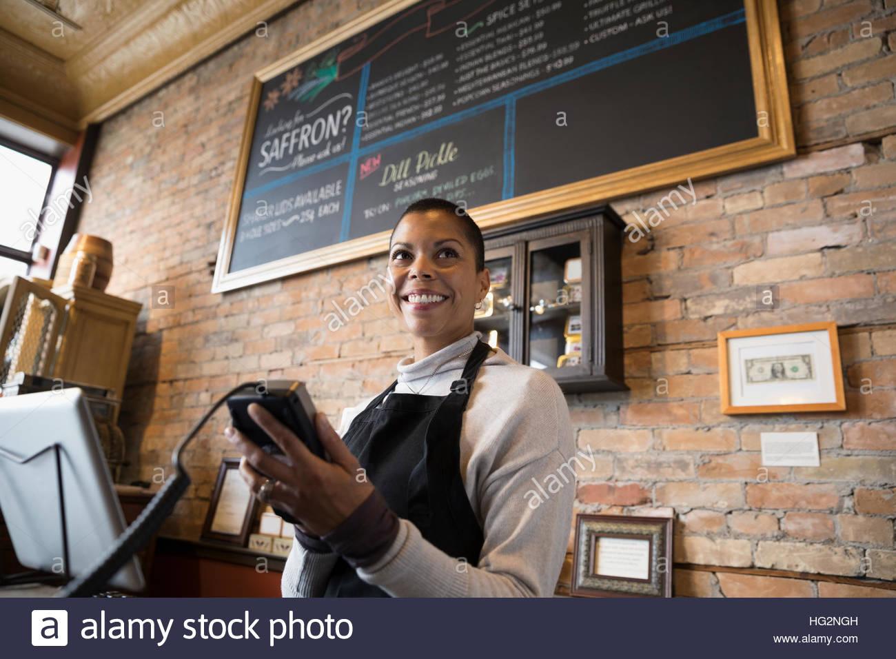 Female spice shop propriétaire à l'aide du lecteur de carte de crédit Photo Stock