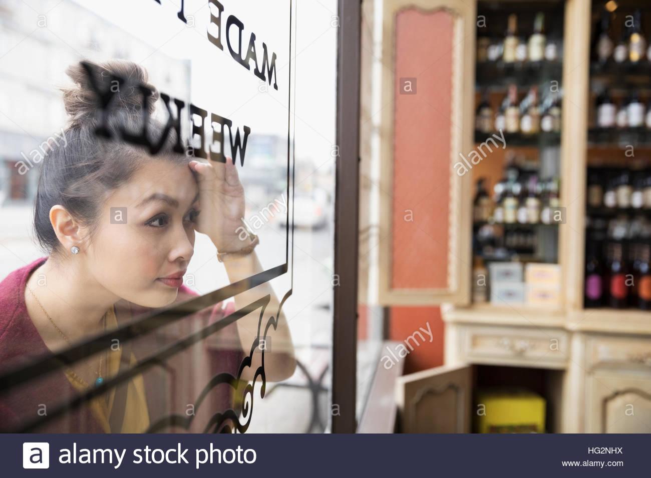 Femme curieuse peeking dans spice shop window Photo Stock