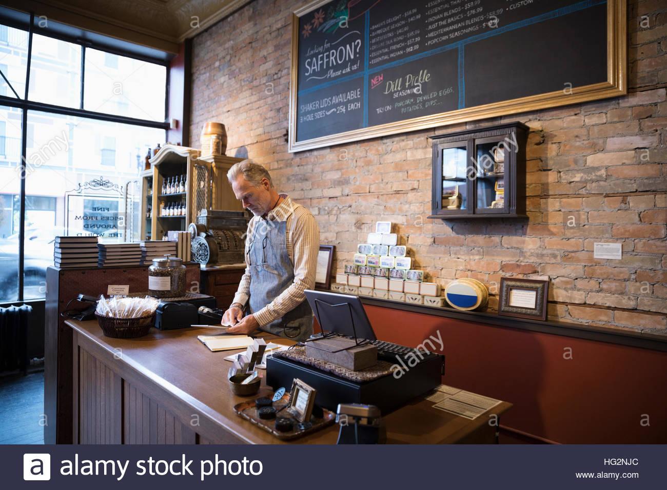 Propriétaire d'une boutique d'épices mâles using digital tablet working at counter Photo Stock