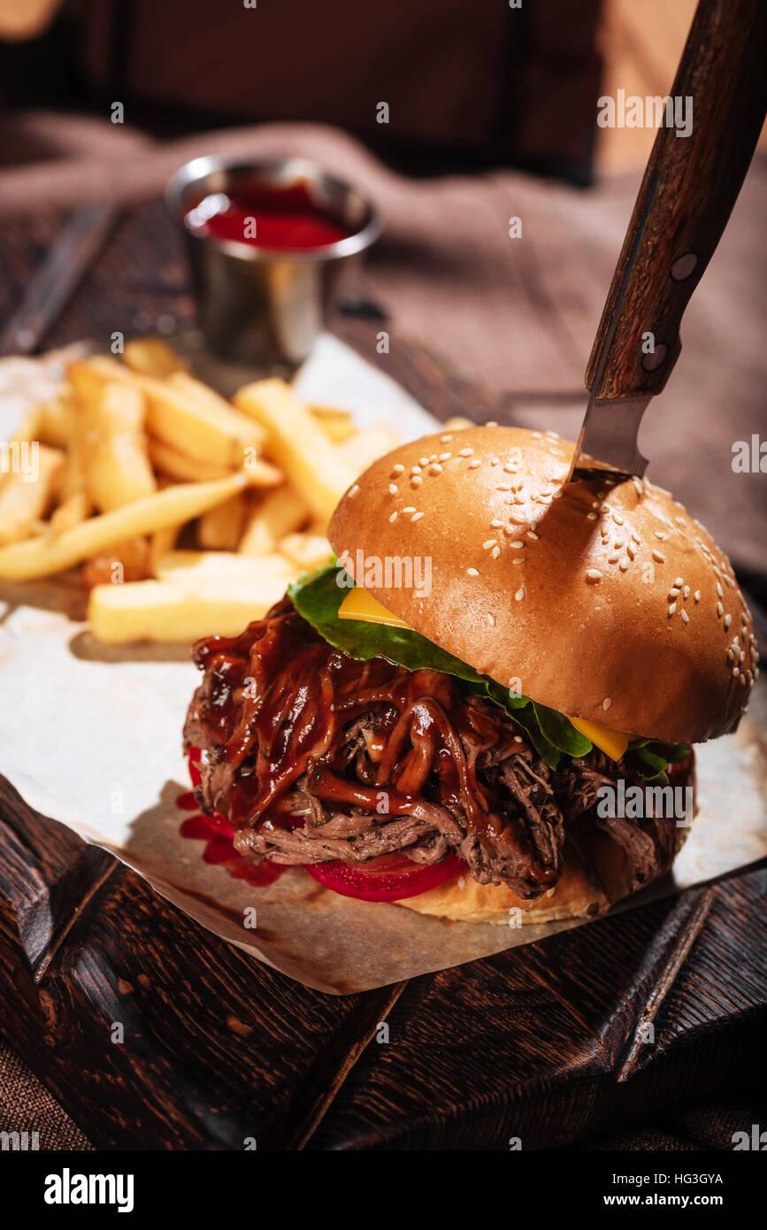 Près d'un burger d'être servis avec frites Photo Stock