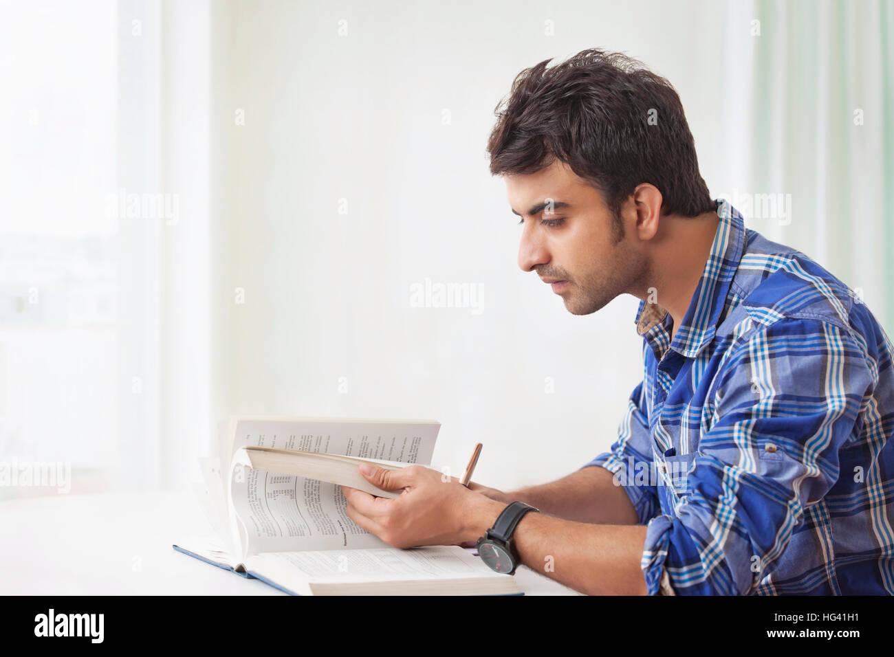 Jeune homme à étudier et prendre des notes Photo Stock