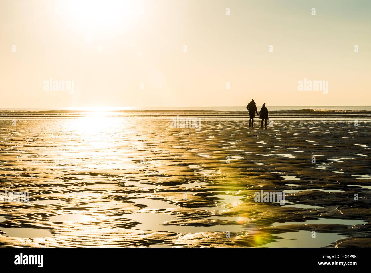 Un couple en train de marcher sur la plage le soir Photo Stock