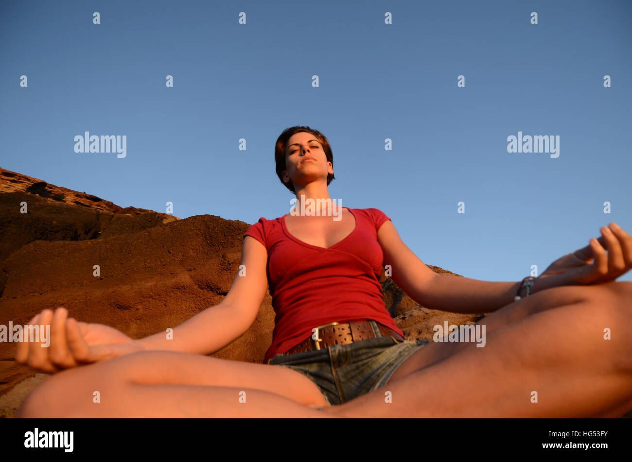 Jeune femme séduisante médite dans lotus pose, en face de la côte. Photo Stock