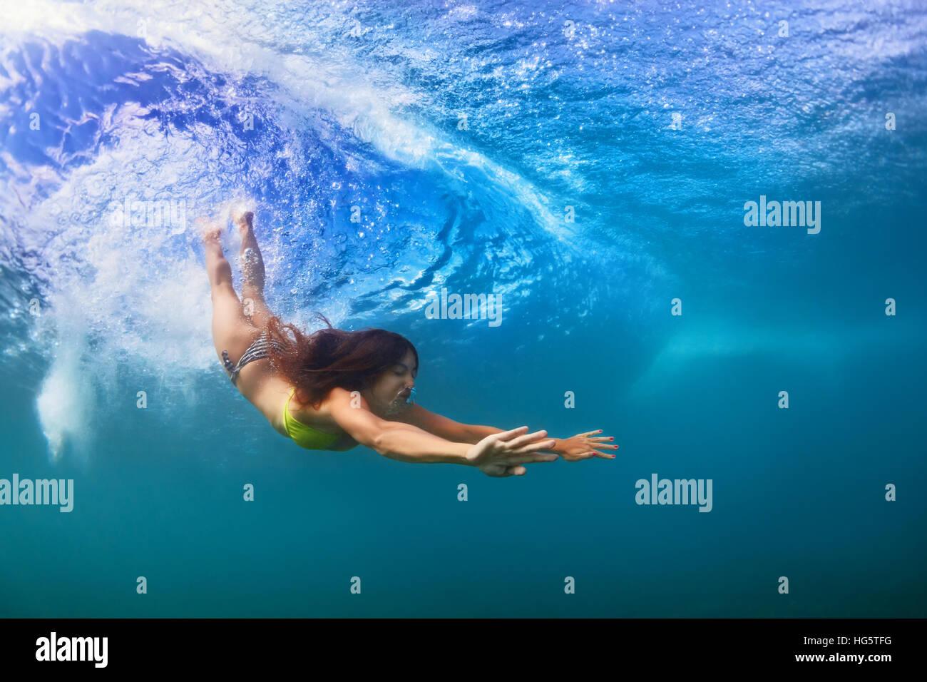 Jeune fille sportive en bikini en action. Fit woman nager sous l'eau, plonger sous la houle à l'effraction. Photo Stock