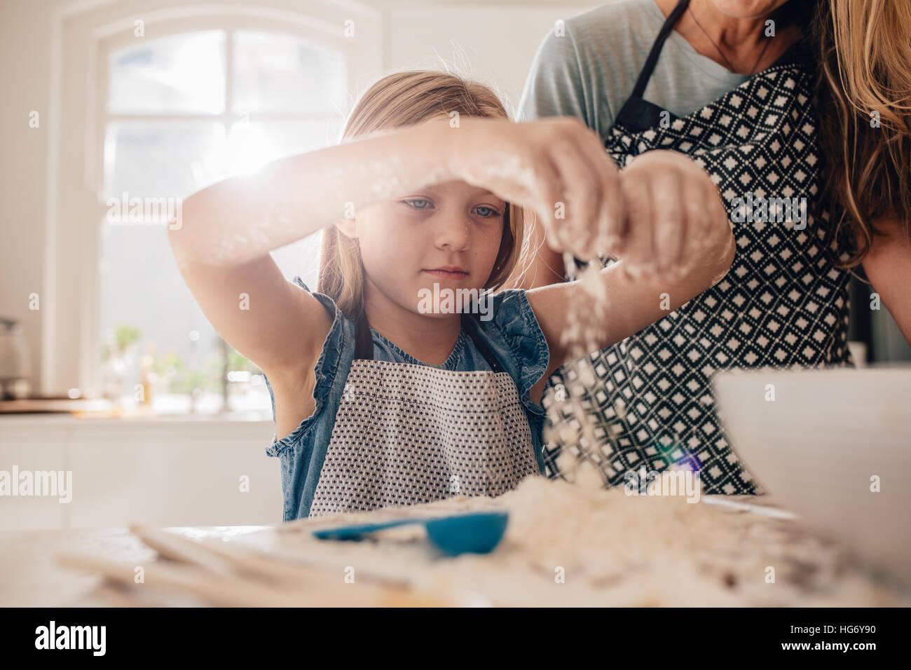 Belle petite fille apprend à cuisiner un repas dans la cuisine. Girl making a la pâte à cuire avec Photo Stock