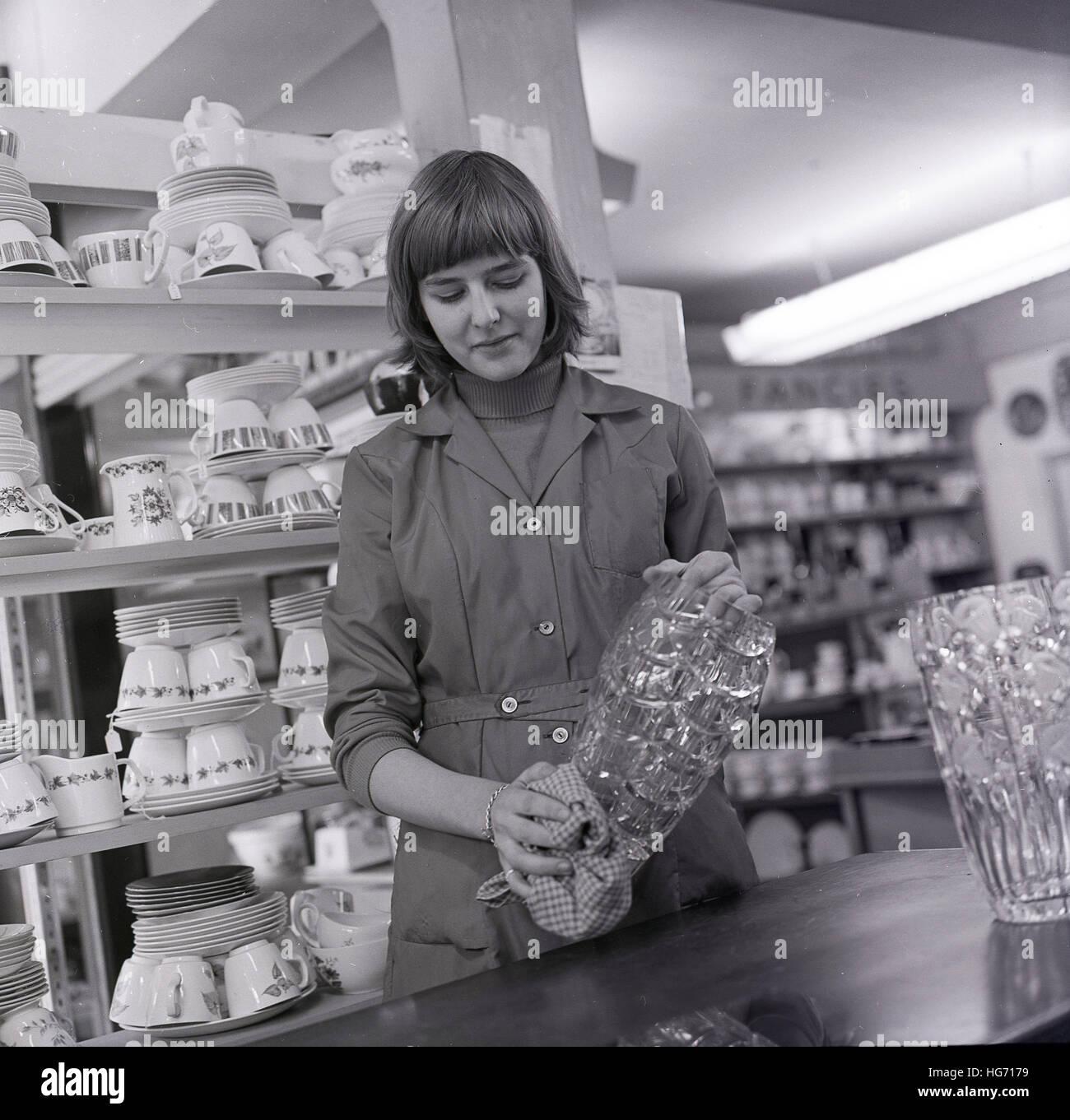 Années 1960, historiques, jeune femme shop assistant nettoie la verrerie vaisselle dans le ministère. Banque D'Images